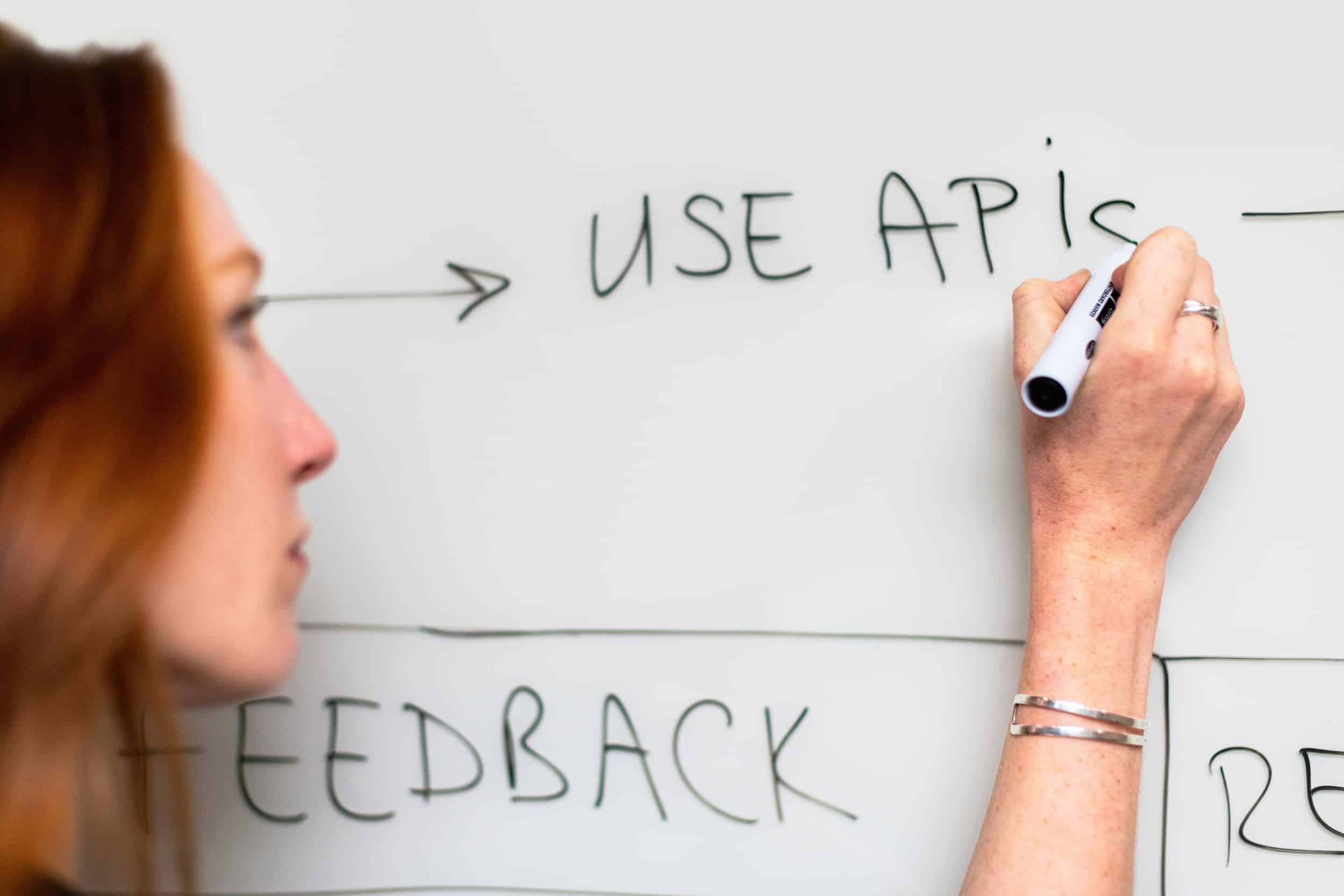 "A whiteboard with the words ""Use APIs"" on it indicating the development process"